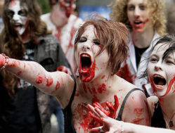 """Two girls dressed and made-up as zombies have fun as they participate in an unsuccessful bid to break the world record for the """"biggest zombie lurch"""" at the Sydney University, 22 September 2007. The event was part of the uni's Verge Arts Festival  but fell well short of the record of 894 set in Pittsburg last year.   AFP PHOTO/Greg WOOD (Photo credit should read GREG WOOD/AFP/Getty Images)"""
